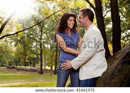 A happy couple relaxing in the park - stock photo