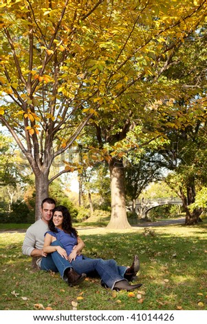 A happy couple relaxing in the park on grass - stock photo