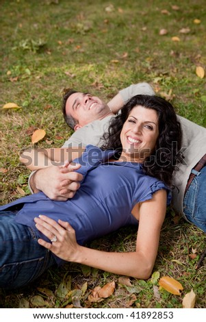 A happy couple relaxing laying in the grass - sharp focus on the woman - stock photo