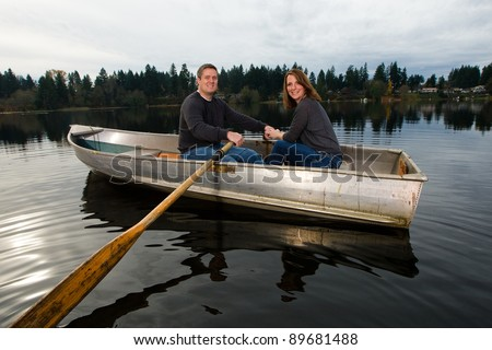A happy couple rowing a small aluminum boat on a lake.  A fun date in nature.