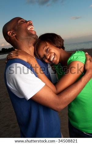 a happy couple runs on the beach at dusk - stock photo