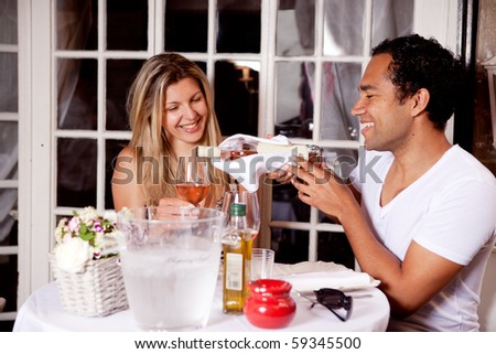 A happy couple sharing a bottle of wine in an outdoor cafe in Europe - stock photo