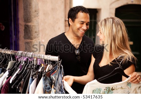 A happy couple shopping at a small street store in Europe - stock photo