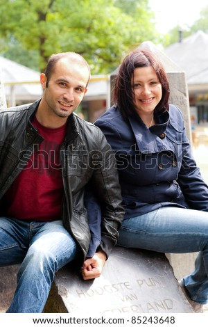 A happy couple sits and holding hands - stock photo
