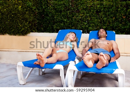 A happy couple sitting in pool chairs relaxing on a holiday - stock photo