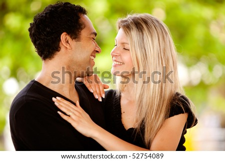 A happy couple smiling and looking at each other in a park - stock photo