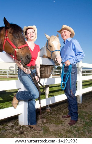 A happy couple standing by their horses - vertically framed - stock photo