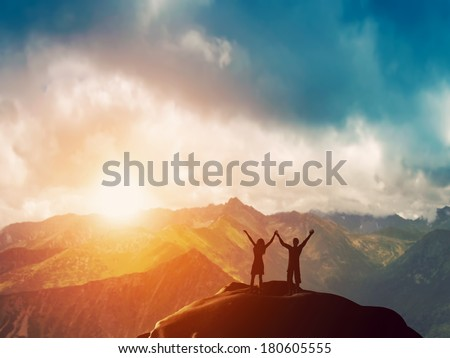 A happy couple standing together on the peak of a mountain with hands raised admiring breathtaking view at sunset - stock photo