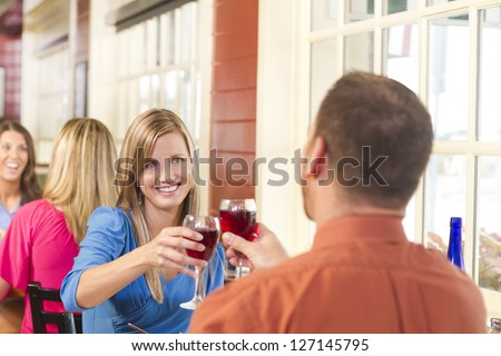 A happy couple toasts with wine at a restaurant with people in the background - stock photo