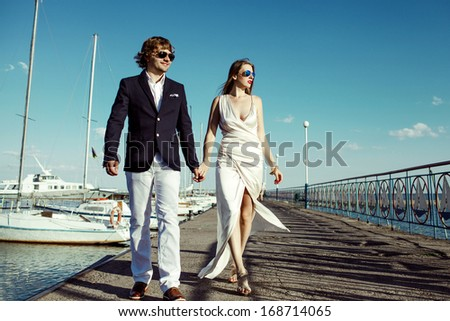 a happy couple walking close to yachts in their wedding day - stock photo