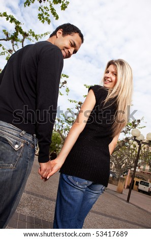 A happy couple walking in the city looking behind at the camera - stock photo