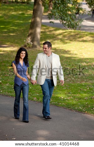 A happy couple walking in the park - stock photo