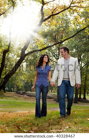 A happy couple walking in the park - looking at each other - stock photo