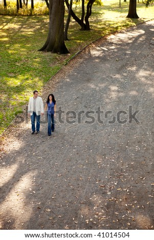 A happy couple walking in the park on a sunny day - stock photo