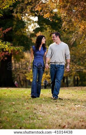 A happy couple walking in the park on grass - stock photo