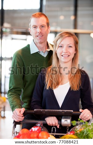 A happy couple with a grocery cart in a supermarket - stock photo