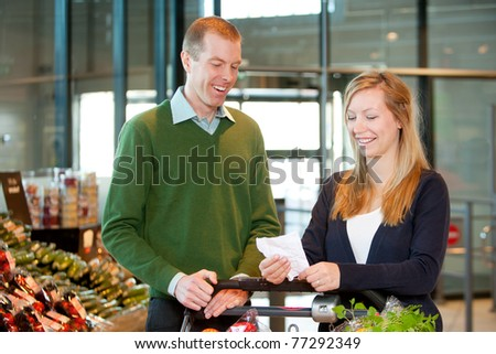 A happy couple with a shopping cart and grocery list in a supermarket