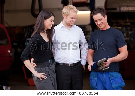 A happy customer couple receiving repair report from smiling man mechanic - stock photo