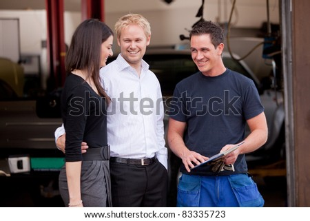 A happy customer couple receiving repair summary from mechanic