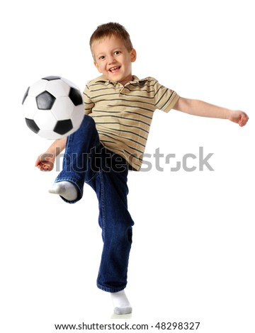 A happy, early elementary boy kneeing a soccer ball.  Isolated on white.  (Motion blur on the ball. - stock photo