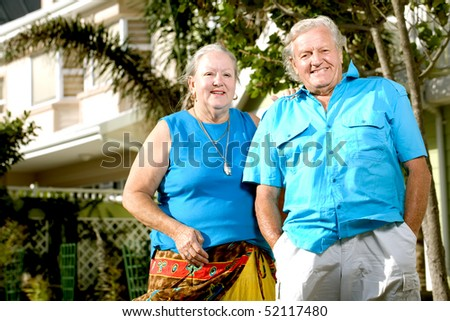 A happy elderly couple standing in front of a house