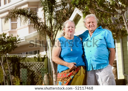 A happy elderly married couple standing in front of a house