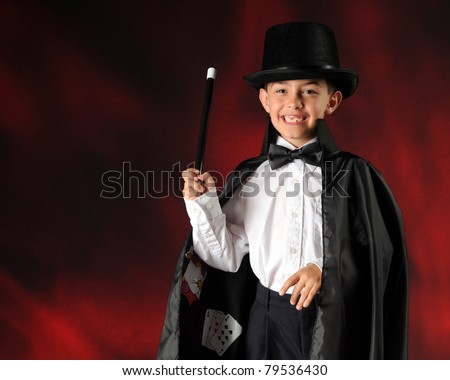 A happy elementary boy performing as a magician.  Horizontal composition with space for your text. - stock photo