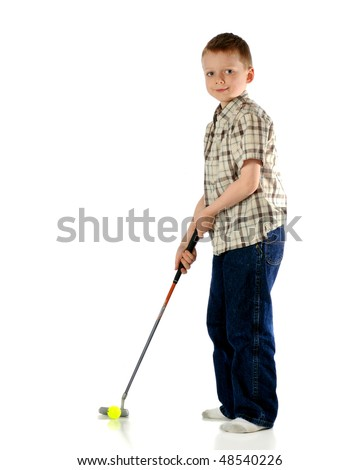 A happy elementary boy practicing golf putting.  Isolated on white. - stock photo