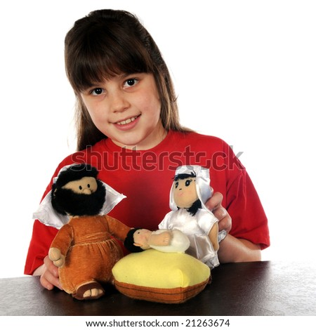 A happy elementary girl playing with large, plush figures of Mary, Joseph and baby Jesus.