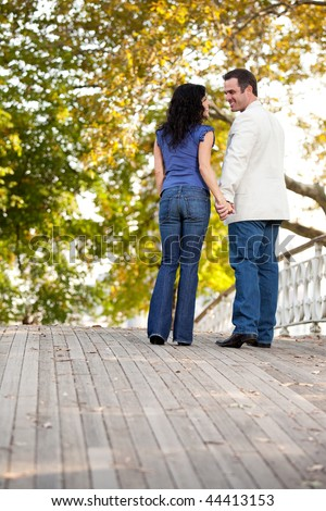 A happy engagement couple walking in the park on a beautiful day - stock photo