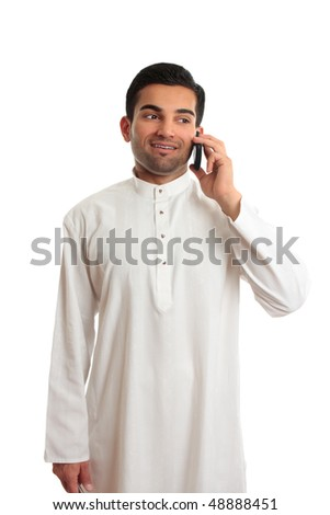 A happy ethnic arab middle eastern man talks happily on a mobile phone.  He is dressed in traditional white kurta, thobe, dishdasha fixed with silver buttons inlaid with burmese rubies. - stock photo