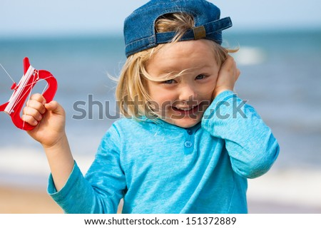 A happy excited and cute young boy flying a kite at the beach. - stock photo