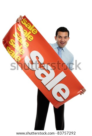 A happy excited businessman, salesman or storeperson holding a vinyl sale banner sign ready to hang. - stock photo