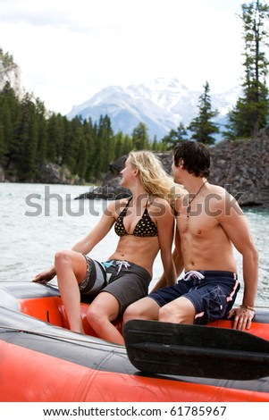 A happy excited couple on a river raft - stock photo