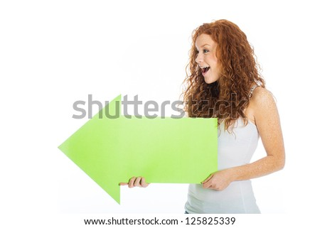 A happy, excited woman looking at something and pointing to the left with a green arrow. - stock photo