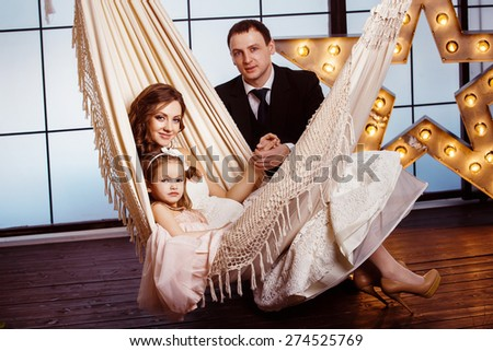 A happy family concept. Beautiful pregnant wife in wedding dress and her cute daughter are sitting in a hammock at a star background while young father is holding her by hand. - stock photo