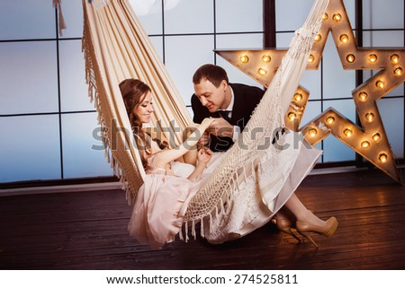A happy family concept. Beautiful pregnant wife in wedding dress and her cute daughter are sitting in a hammock at a star background while young father is kissing her by hand. - stock photo
