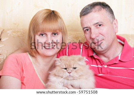 A happy family enjoying their free time at home with fluffy cat - stock photo