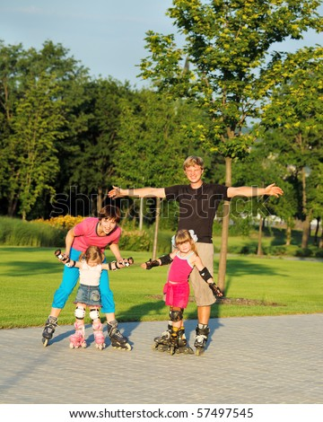 A happy family enjoying weekend in roller skates - stock photo