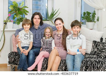 A happy family from father, mother, two sons and daughter are sitting at sofa in living room