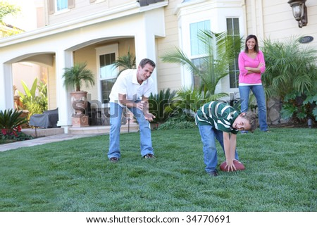 A happy family having fun at  home playing football sports - stock photo
