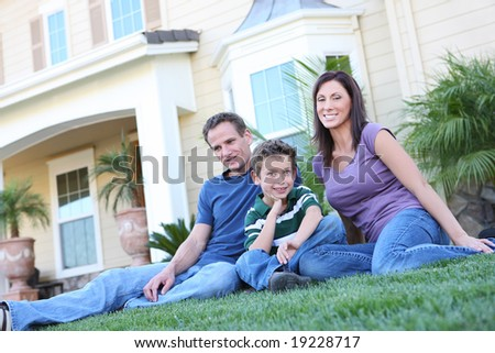 A happy family having fun outdoors in front of their home - stock photo