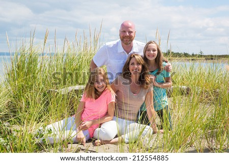 A happy family in the grass at the beach - stock photo