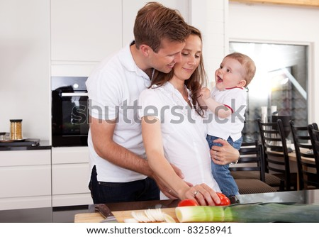 A happy family in the kitchen preparing food and having fun