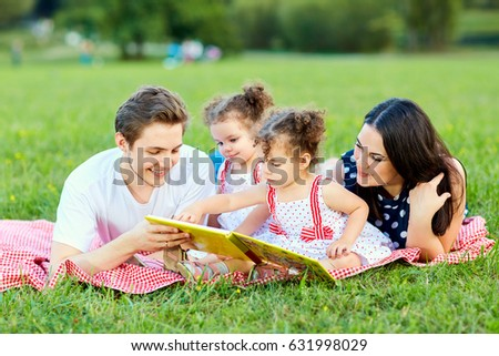 A happy family is reading book in the park.
