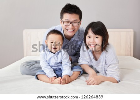 A happy family lying on white bed in the bedroom with gray wall for copy space, asian people - stock photo
