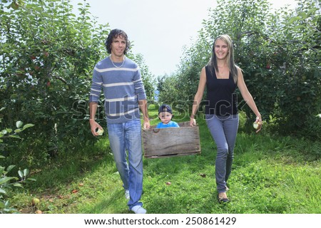 A happy family of attractive caucasian catch apple  - stock photo