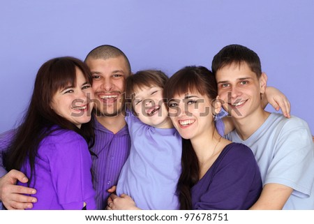 A happy family of five on a light purple background