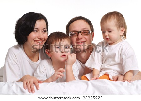 A happy family of four in the white jerseys on a bed on a isolate background