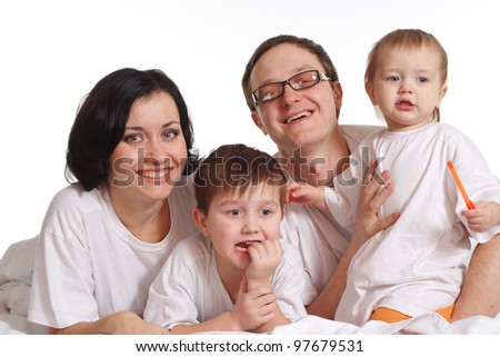 A happy family of four in the white jerseys on a bed on a white background